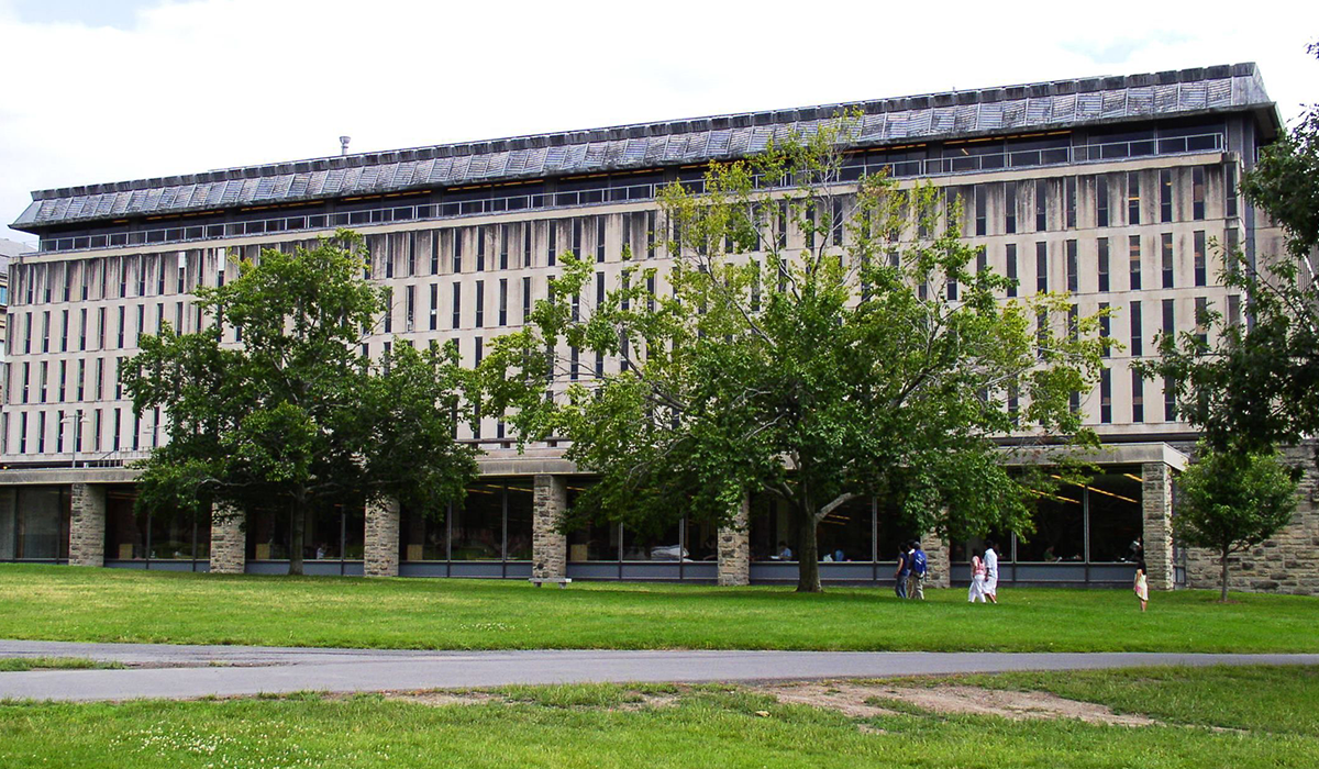 Olin Library at Cornell University with students walking through the grass